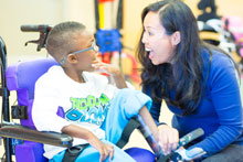 woman interacting with child in wheelchair