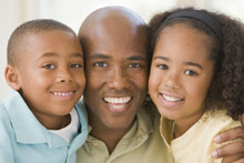 African-America father with young son and daughter