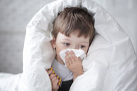 boy in blanket wipes nose