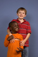 Older boy with arm around a younger boy, both smiling